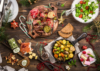 Flat lay of Delicious Christmas themed dinner table with roasted meat steak, appetizers and desserts. Top view. Holiday concept. Fototapete