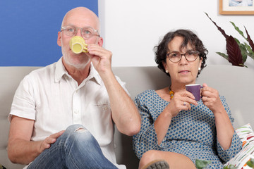 Happy senior couple drinking coffee, in their sofa