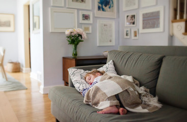 little girl taking a nap on her living room couch
