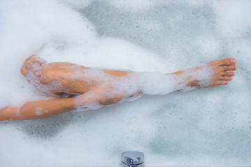 Closeup of woman's legs in bathtub