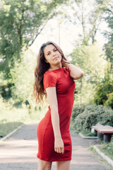 Beautiful girl model in a park on the road posing for photo camera in red board
