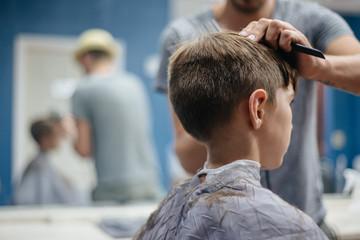 Boy gets a haircut at a barber shop
