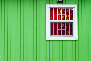 Green wooden wall with window with red curtains