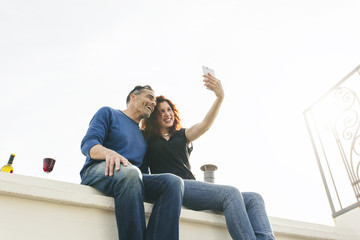 Beautiful couple taking a picture of themselves with smart phone on the rooftop.