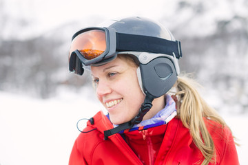 Women with helmet and googles ready for skiing with a smile