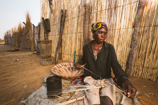 African Hambukushu woman weaving reed baskets