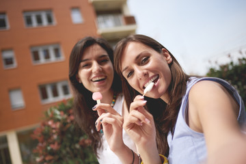Girl taking outdoor selfie of her and friend eating ice cream