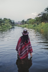 Woman walking in river wearing a red poncho and hat