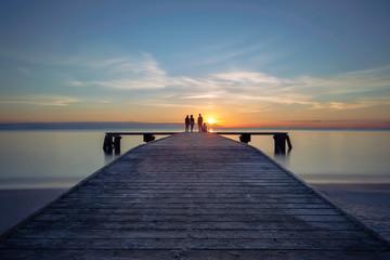 friends standing on ocean at sunrise
