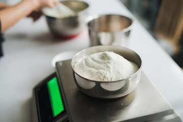 Bakery chef weighing flour on the digital scale
