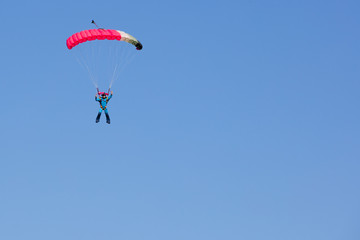 Foto op Aluminium Luchtsport skydiver in blue costume on black and pink parachute fly to sky