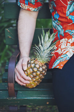 Man in hawaiian shirt sitting on bench with a fresh pineapple