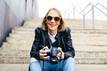 Portrait of a mature woman holding her camera sitting on stairs.