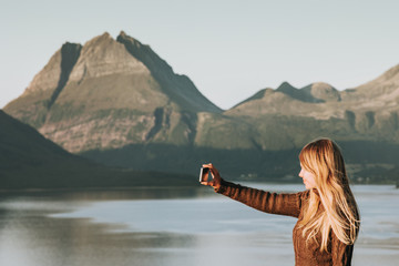 Woman tourist taking selfie by smartphone Travel Lifestyle concept adventure vacations outdoor Norway sunset mountains and sea landscape