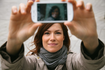 woman taking a self-portrait with the camera