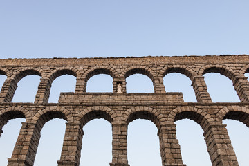 Upper side of roman aqueduct, with detail of Virgin of the Aqueduct, located in the central niche of the monument has since the Plaza del Azoguejo, Segovia, Spain