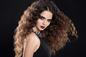 Beauty girl hair. Curly hairstyle. brunette girl with healthy long hair, beauty makeup. Beautiful woman with marsala matte lips, blowing hairstyle isolated on black background