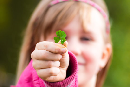 Four leaf clover in small hand of young girl