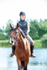Young teenage girl riding horseback from lake at early morning