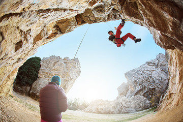 male rock climber climbs on a rocky wall at winter sunny day. Man climber in warm clothes on yellow cliff.
