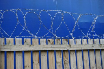 Security fence with barbed wire and blue tarp