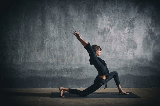 Beautiful sporty fit yogini woman practices yoga asana Virabhadrasana 1 - warrior pose 1 in the dark hall