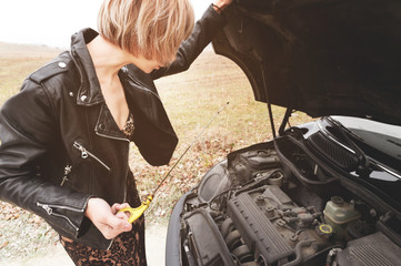 Girl opening the hood of her car checks the engine oil level