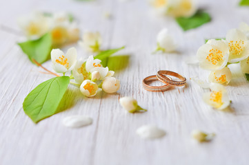 Wedding rings lie on a wooden white background with jasmine branches. Symbol of love and marriage. Bride's traditional symbolic accessory. Floral composition with jasmine flowers.