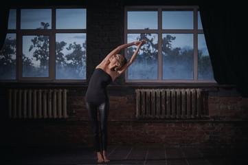 Beautiful woman practices yoga asana Tiriaka Tadasana in the dark hall