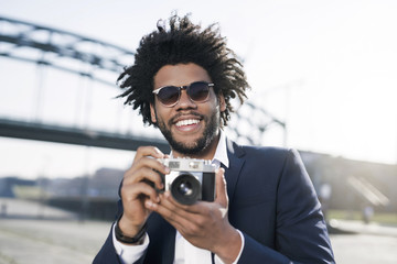 Smiling man in suit at the riverside holding a vintage camera