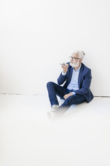 Mature man sitting on the floor using cell phone