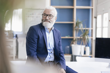 Confident mature man with beard and glasses in office