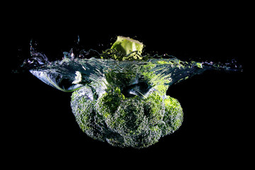 Cauliflower falling into water, isolated against black background