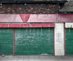 abandoned closed shop with decaying facade and green shutters