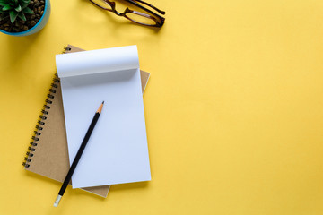 notebook and pencil on yellow desk Wall mural