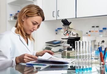 Young European female scientist checks her laboratory journal