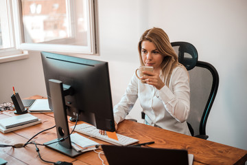 Attractive blonde businesswoman working with computer and drinking coffee in office.