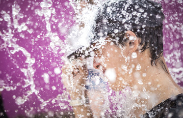 Young man standing in drops of water spray