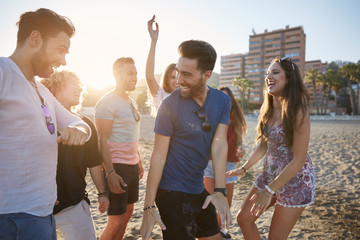 Young man dancing with friends on beach laughing