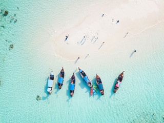 Top view or aerial view of longtail boats on crystal clear water along the sand beach in Phuket Thailand