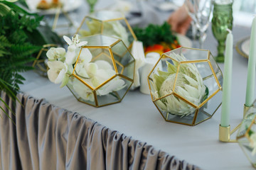 Golden cubes with white flowers stand on grey table for newlyweds