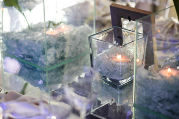 Glass vase with white crystals and candle stands on a mirror table