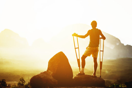 Disabled man stands crutches mountains backdrop