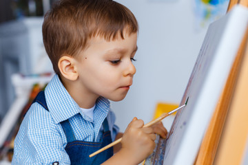 Cute, serious and focused, white three years old boy in blue shirt and jeans apron drawing on canvas standing on the easel. Concept of early childhood education, talent, happy family or parenting