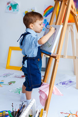 Cute, serious and focused, white three years old boy in blue shi