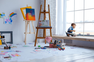 Cute, happy, white boy in blue shirt and jeans sitting with palette in studio and looking to window. Little child among colorful pictures. Concept of early childhood education, happy family, parenting