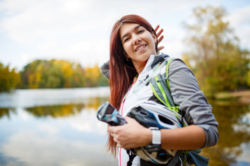 Photo of happy brunette with backpack and bicycle helmet