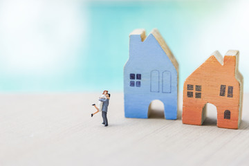 Happy couple standing in front of miniature wooden house with space on blurred background