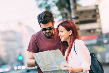 Young couple traveler lost in the city using map