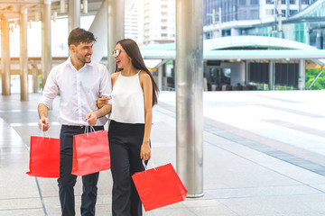 Happy couple hold shopping bags walking in the city and beautiful woman wearing sun glasses.